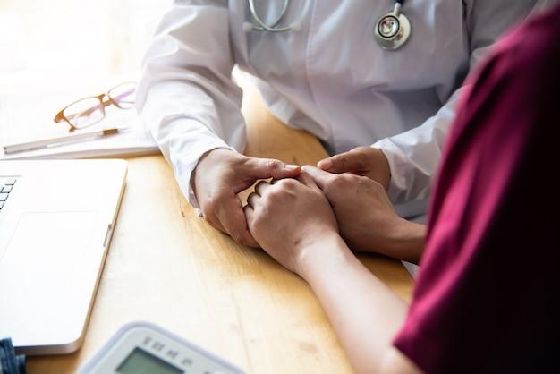 彼女の女性患者を安心させる医師の手