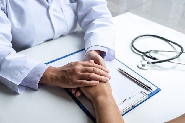 病院での診察中のサポートへの励ましと共感を安心させる患者に触れる医師の手。