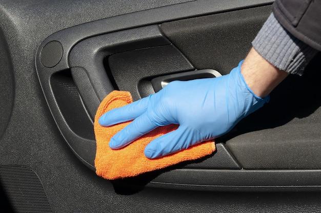 青い保護手袋をはめたドライバーの手が車の内部ハンドルを布で拭いています