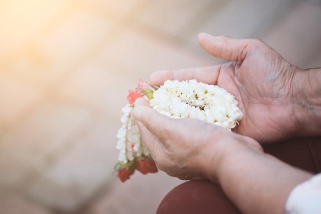 ソンクラーン祭りを祝うために美しい花輪を保持する高齢者の手