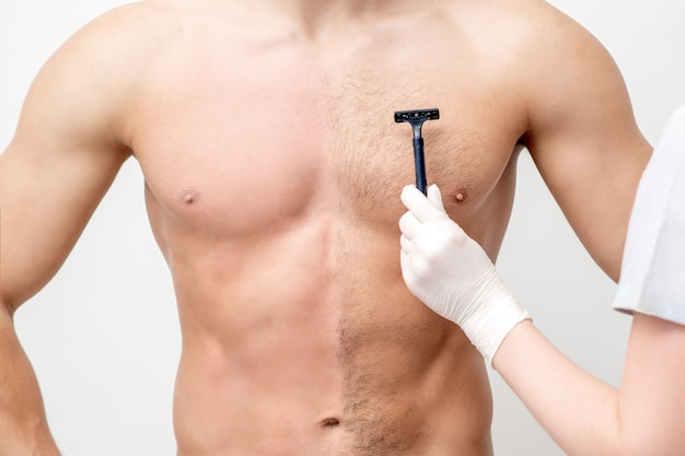 女性美容師の手が若い男の胸をかみそりで剃る。脱毛の概念