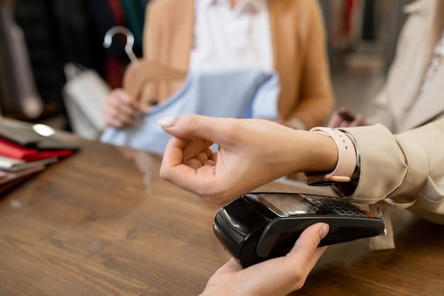 カウンターのそばに立っている間、ブティックや衣料品部門で新しい服の代金を支払うスマートウォッチを持つ女性の顧客の手