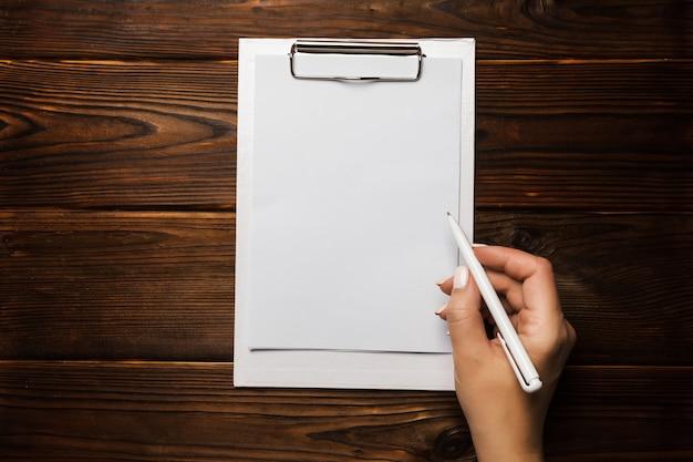 Рука женщины с белой ручкой и клипбордом