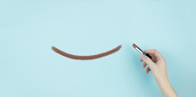 Рука женского письма улыбки с коричневой помадой на синем фоне.