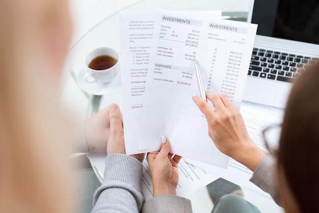 銀行口座を開く予定のクライアントに詳細を説明しながら、ドキュメントで合計を指しているペンで財務顧問の手