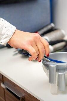 Рука парикмахера готовит краситель в миске для окрашивания волос в парикмахерской