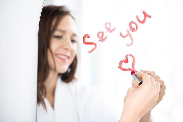 Рука счастливая брюнетка девушка пишет, увидимся и рисует сердце с помадой на зеркале после утреннего душа