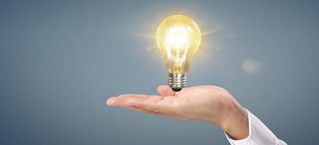 Рука держит освещенную лампочку. идея инновация вдохновение концепция