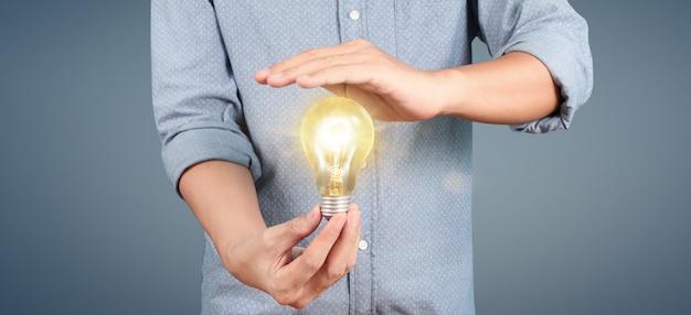 Рука проведения освещенной лампочки. концепция инновационного вдохновения