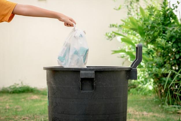 ビニール袋に入ったゴミを庭のゴミに捨てる人間の手。