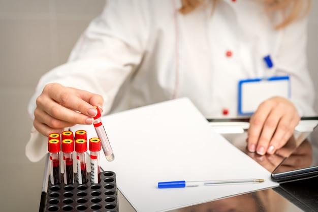 Рука лаборанта или медсестры берет пустую пробирку для анализа крови из стойки в исследовательской лаборатории