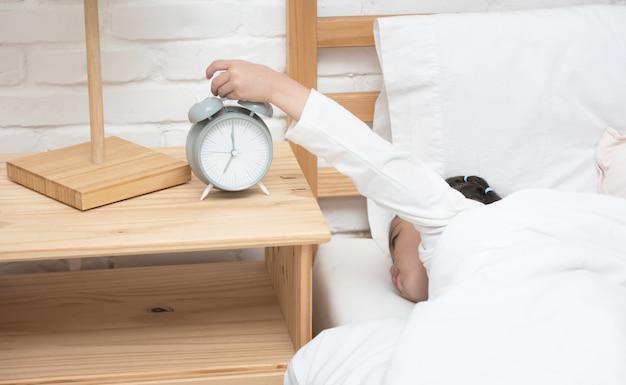 Рука маленького азиатского будильника касания девушки пока она кладя положила звенеть стопа часов.