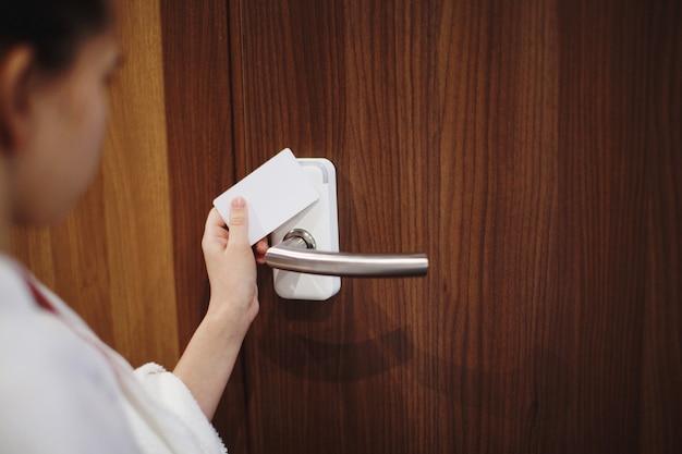 茶色のドアのロックを解除するために白いキーカードを保持している小さな子供の女の子の手。