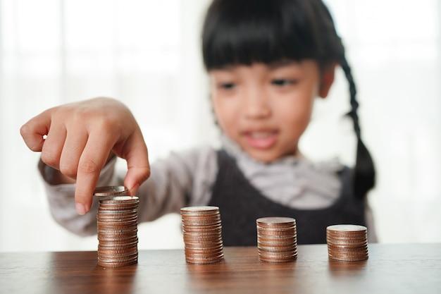 コインのスタックにコインを置く小さな子供の女の子の手