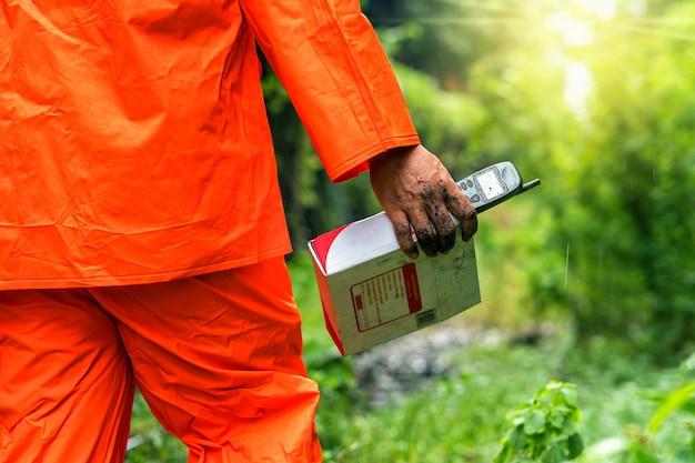 Рука горничной, держащей старый мобильный с почтовым ящиком над лесом