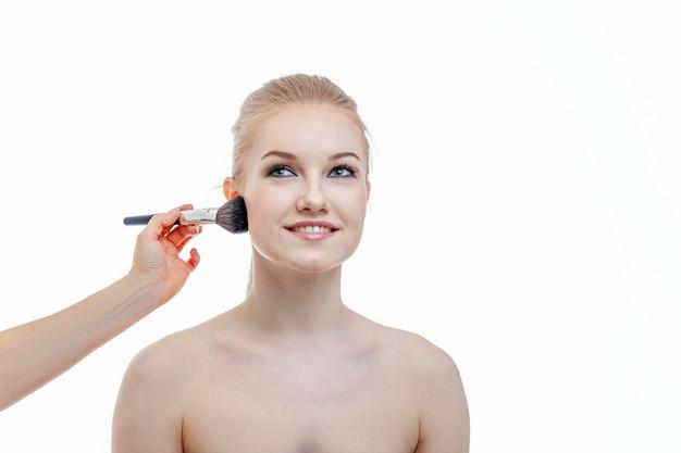 Рука мастера состава прикладывая порошок для модели молодой женщины на белой стене. профессиональное нанесение макияжа от художника. красивая девушка лицо с идеальной кожей. макияж деталь в процессе.