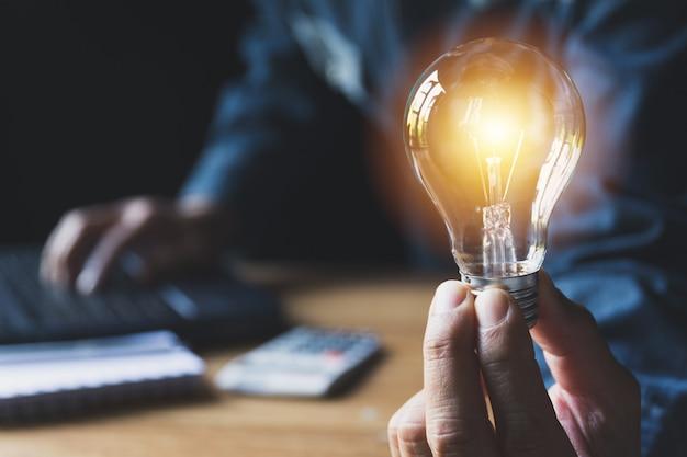 会計と創造的な概念のための電球を持つ男性の手。