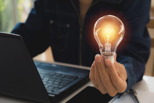 イノベーションと創造的なコンセプトのための電球を持つ男性の手。