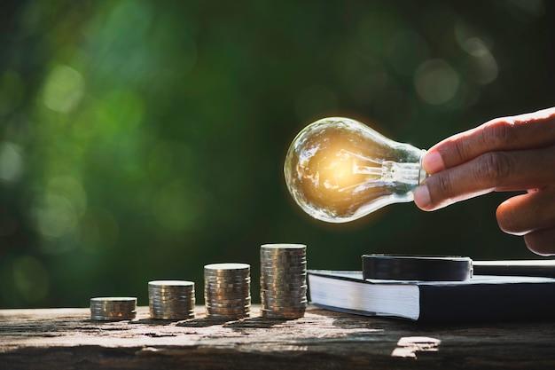会計、アイデア、創造的な概念のためのコインとコピースペースのスタックで電球を保持している男性の手。