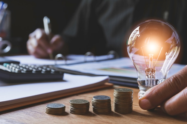 Рука мужчины держа электрическую лампочку с стогом монеток для бухгалтерии и творческой концепции.