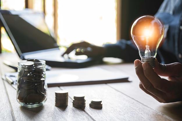 コインのスタックで電球を持っている男性の手