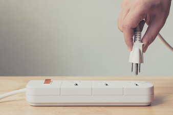 Hand of male or female unplugged plug into socket to save energy