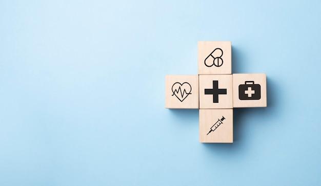 Рука человека, устраивающего укладку деревянных кубов со значком здравоохранения, медицинским на синем