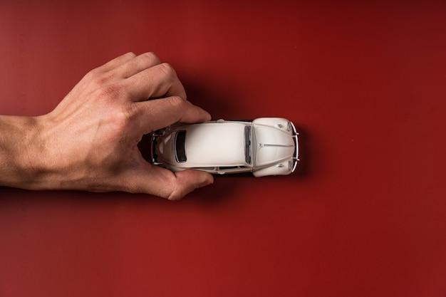 남자의 손을 잡고 빨간색 미니어처 장난감 자동차