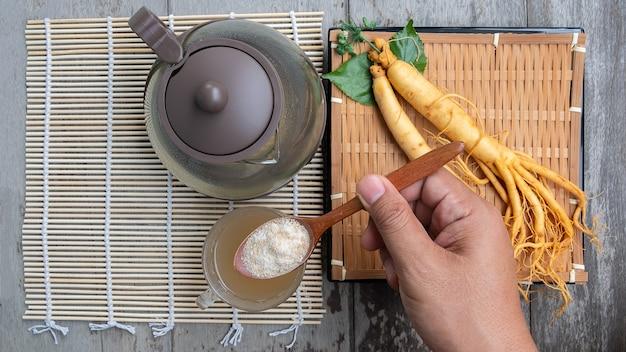 お茶の高麗人参の粉末でスプーンを持っている男の手、健康的な飲み物の概念