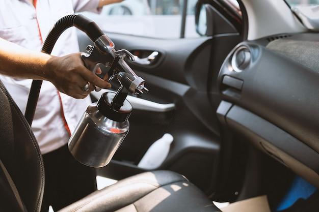 人の手が車の中でcovid-19ウイルスをソフトフォーカスで壁に光を吹きかけています。