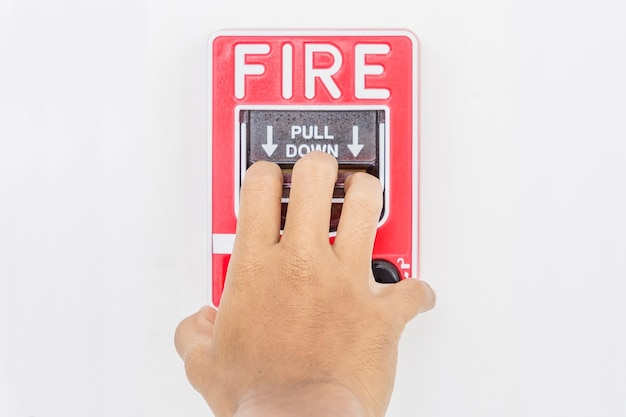 非常事態のための背景として白い壁に火災警報スイッチを引っ張る男の手
