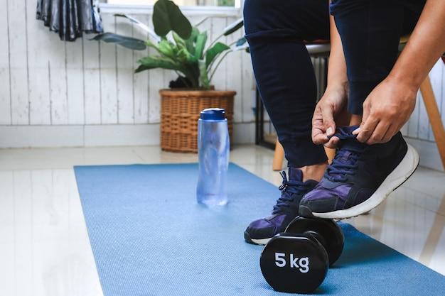 スニーカーを結ぶ男の手は、ボトルの水とバーベルで自宅で運動の準備をします