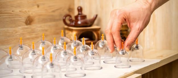 마사지 치료사의 손은 스파의 테이블에서 진공 유리 병을 가져옵니다