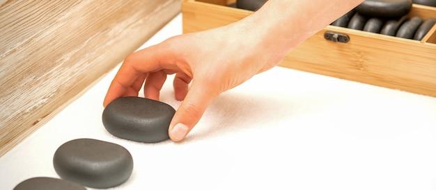 Рука массажиста раскладывает массажные камни на столе