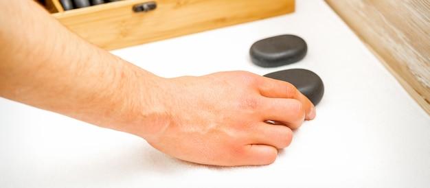 Рука массажиста берет черные массажные камни со стола в спа-салоне.