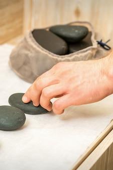안마사의 손은 스파 테이블에서 뜨거운 검은 마사지 돌을 걸립니다