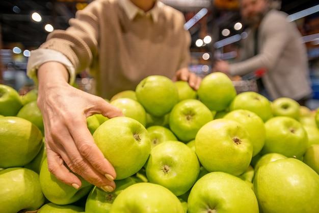 Рука зрелой женщины-потребителя берет свежее яблоко бабушки смит, стоя у кучи фруктов во время посещения супермаркета