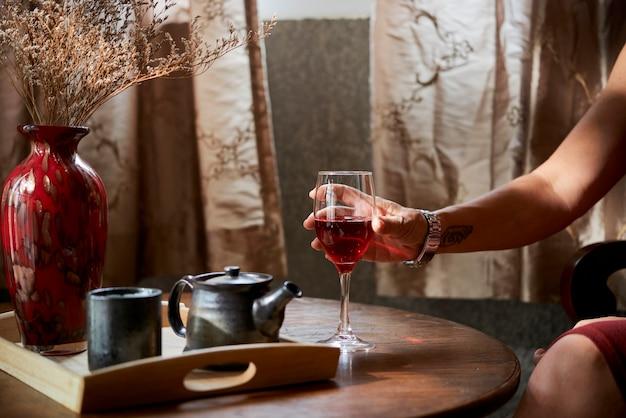 コーヒーテーブルから赤ワインのガラスを取る成熟した女性の手