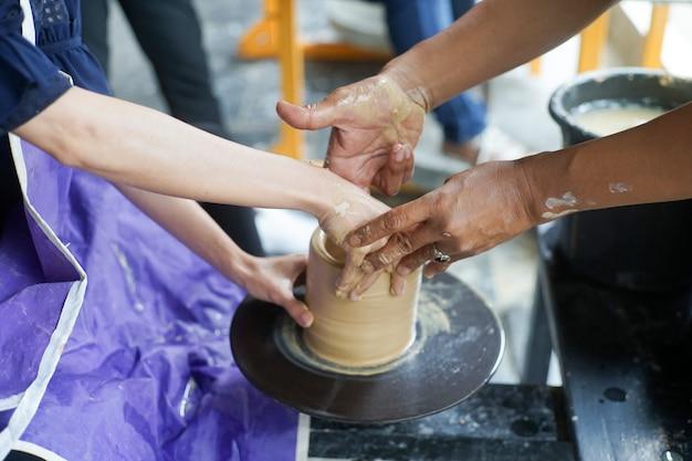 Рука женщины средневекового мастера делает горшок из глины