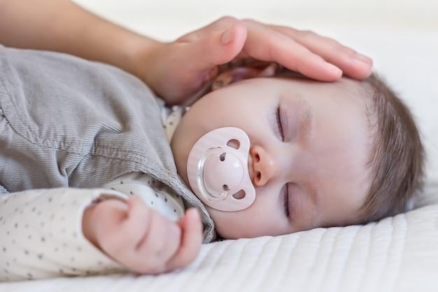 Рука матери, лаская ее милую девочку с соской, спящей над белым покрывалом