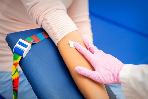 病院で血液サンプルを採取した後、若い女性の腕に綿棒を適用する看護師の手