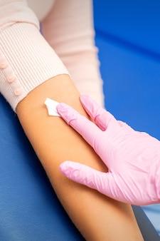 병원에서 혈액 샘플 후 젊은 여성의 팔에 면봉을 바르는 간호사의 손