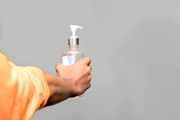 人々の手は、アルコールジェルまたは抗菌石鹸を適用してポンプボトルを押し、手を洗浄して細菌や細菌を除去します。