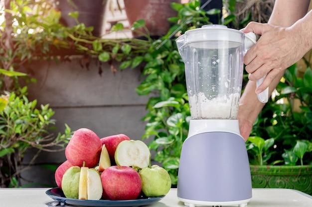 사람들의 손이 전기 믹서기를 사용하여 신선한 사과와 구아바 주스를 만들고 있습니다.