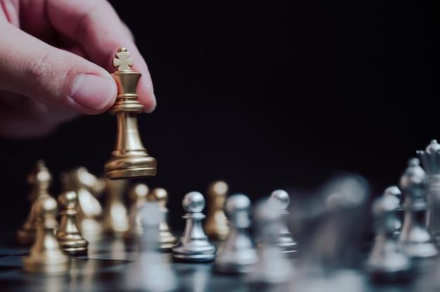金のポーンを置くプレーヤーのチェス盤ゲームの手