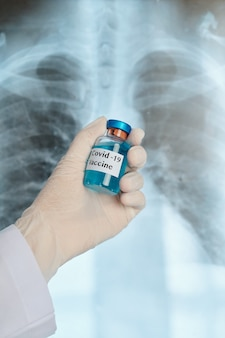 폐 엑스레이에 대한 covid-19 백신을 들고 고무 장갑을 착용 한 폐 질환의 손