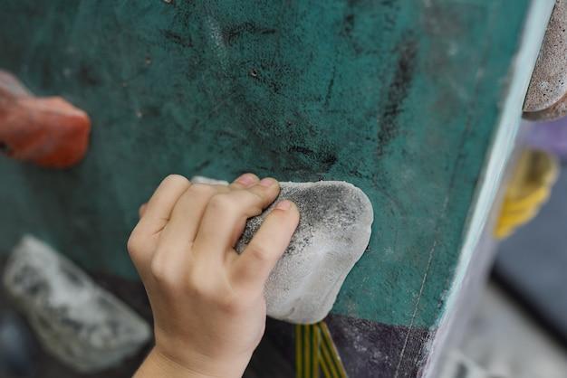 ジムやレジャーセンターでのトレーニング中に登山装備の小さな岩の上の少年の手