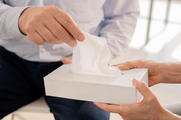 Рука старшего мужчины берет бумажную салфетку из коробки, которую предлагает одноклассник или консультант