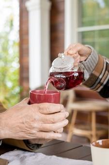Рука старшей жены с чайником наливает черный травяной чай в керамическую кружку, которую ее муж держит над столом, который подают на завтрак на открытом воздухе