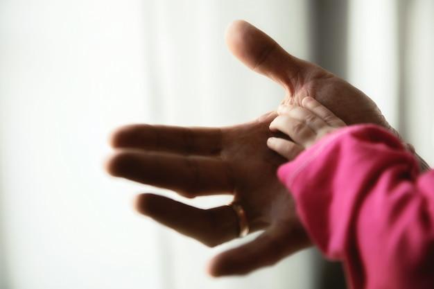クローズアップでお父さんの手のひらに小さな子供の手。父は新生児の手を手に持っています。家族:親と赤ちゃんの手。子育て、親の世話、父の日の概念。画像サイトのコピースペース